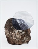 A framed photograph of a rock with a cutout of a photograph of a mountain ridge