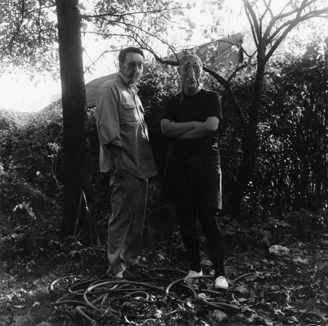 Black-and-white photograph of two people in rubber masks standing against a hedgerow