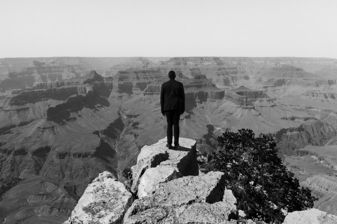 Black-and-white horizontal photograph of a figure silhouetted against an expanse of the Grand Canyon.
