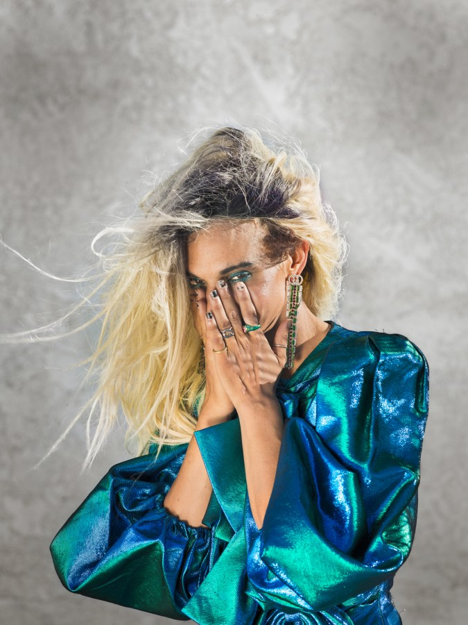 Color photographic portrait of a woman in an iridescent blue top covering her face with her hands
