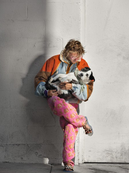 Color photograph of a man in a colorful mismatched outfit holding a black and white dog while leaning on a white wall