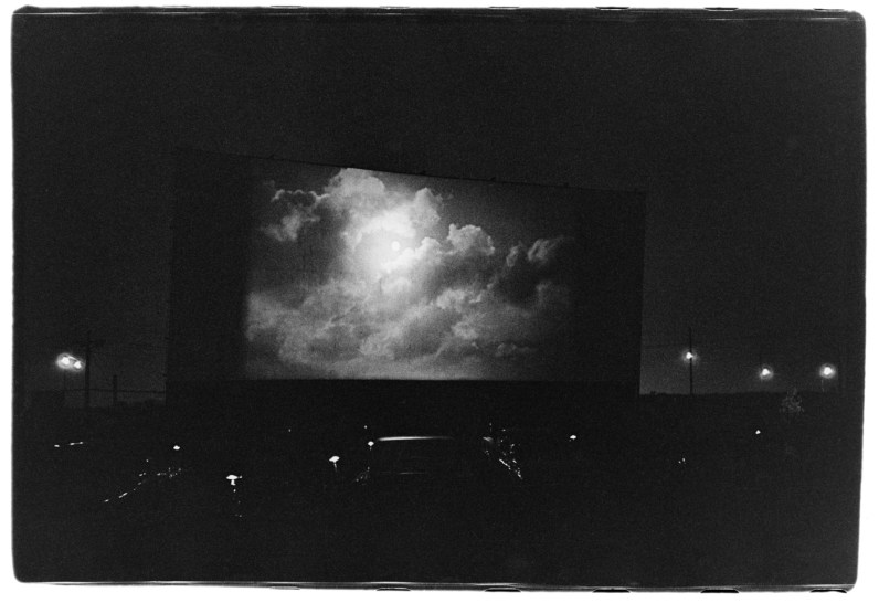 Black-and-white photograph of a drive-in theater at nighttime with clouds on screen