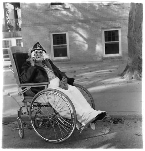 Black-and-white photograph of a masked figure in a wheelchair with a building and tree in the background