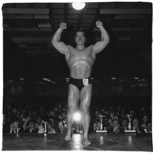 Black-and-white photograph of a body builder flexing on stage with his back to the crowd