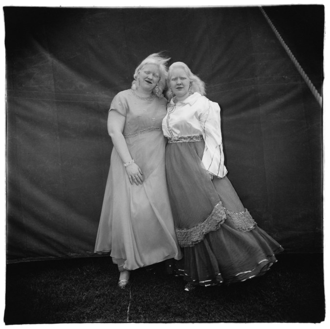 Black-and-white photograph of two women in dresses standing in front of a tent