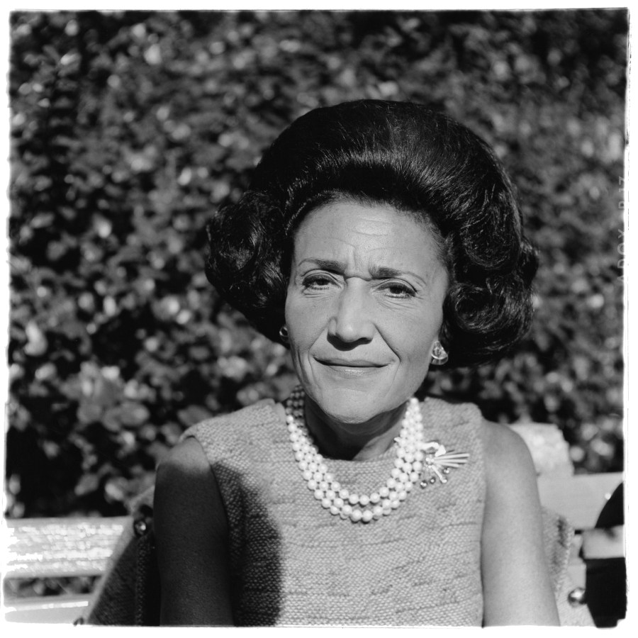 Black-and-white photograph of a woman with dark hair wearing a pearl necklace and broach