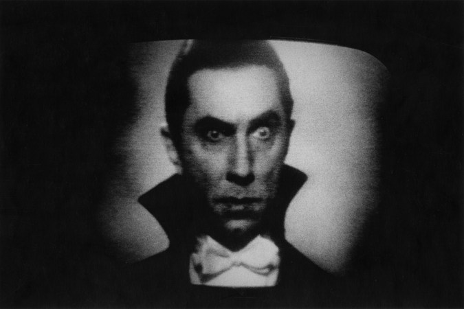 Black-and-white photograph of Dracula with one eyebrow raised on a movie screen