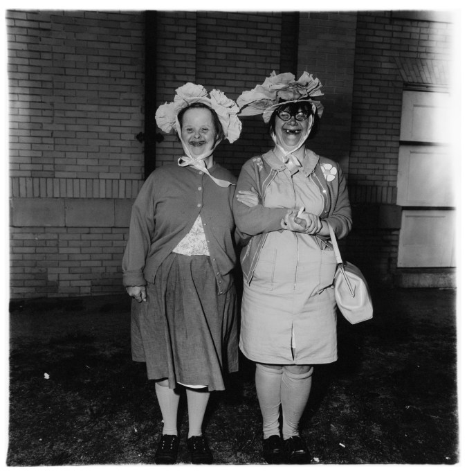 Black-and-white photograph of two women wearing hats with a building in the background