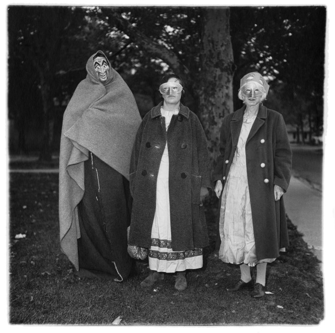 Black-and-white photograph of three masked figures in coats with trees in the background