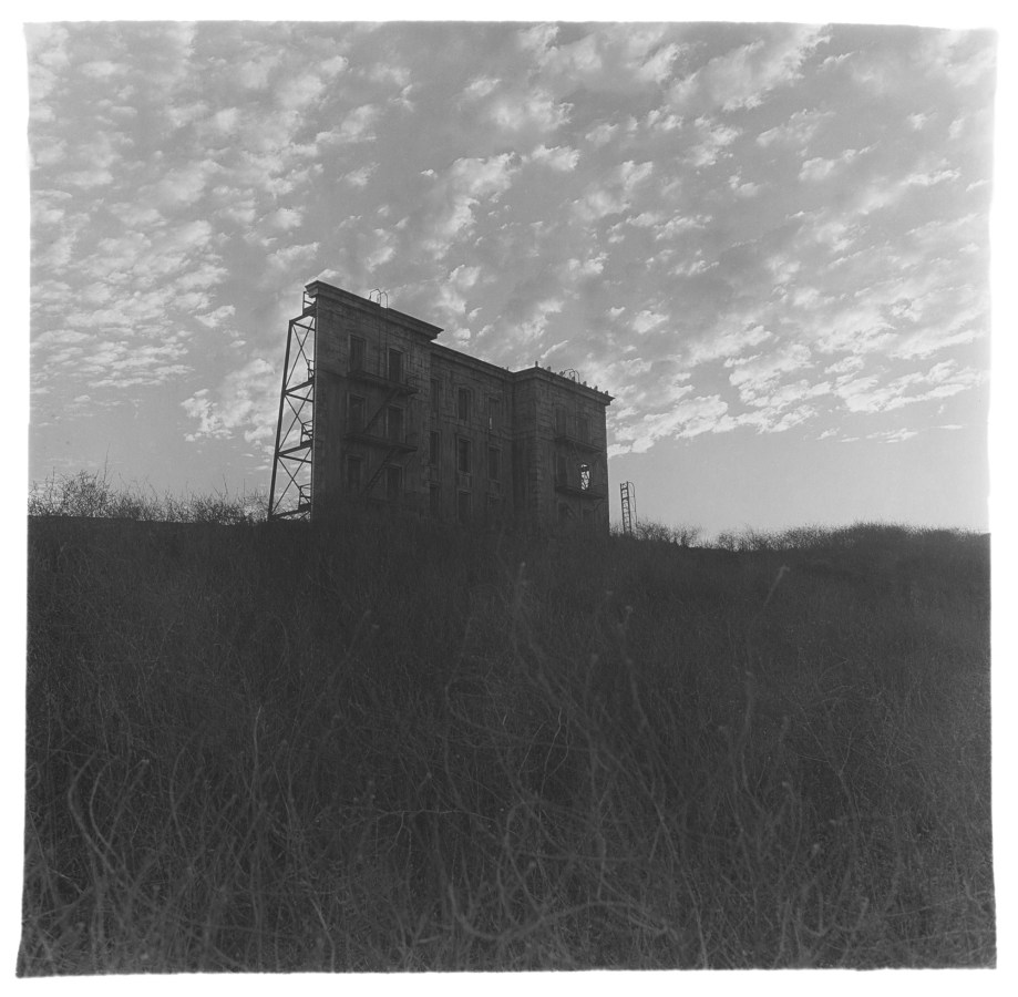 Black-and-white photograph of a fake building facade with grass in the foreground and a scattered clouds in the sky