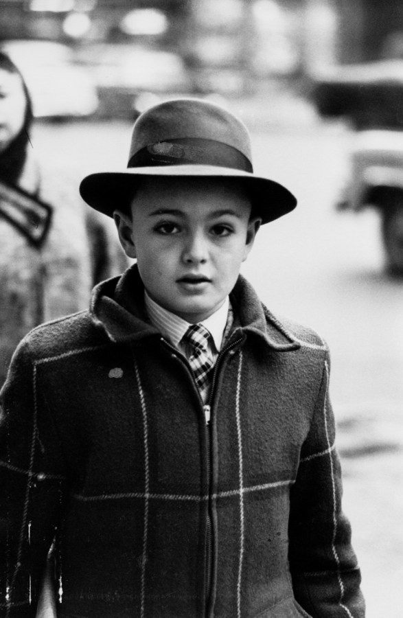Black-and-white photograph of a boy wearing tie, coat, and hat with full brim