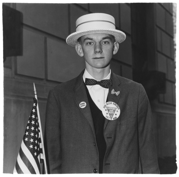 Black-and-white photograph of a man with a hat, bowtie, jacket with political lapel pins holding an American flag