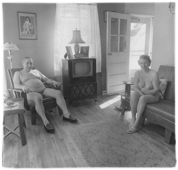 Black-and-white photograph of a nude man and woman sitting in a living room with a television at the center