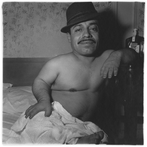 Black-and-white photograph of shirtless man wearing a hat sitting in bed with a towel on his lap