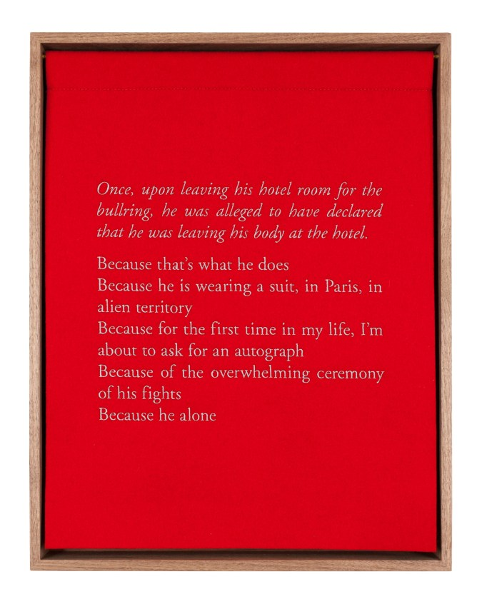 A wooden box with a red curtain, embroidered with white text describing the bullfighter Jose Tomas