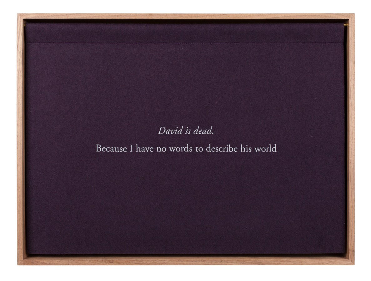 """A wooden box with a purple curtain, embroidered with white text """"David is dead. Because I have no words to describe his world."""""""