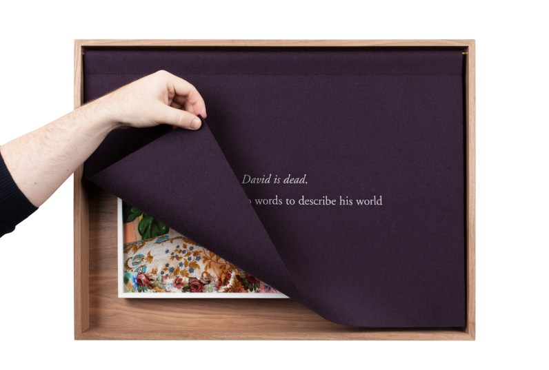 A wooden box with a purple curtain, embroidered with white text, the curtain lifted by a hand