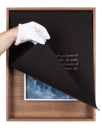 A wooden box with a black curtain, embroidered with white text. The curtain lifted by a hand.