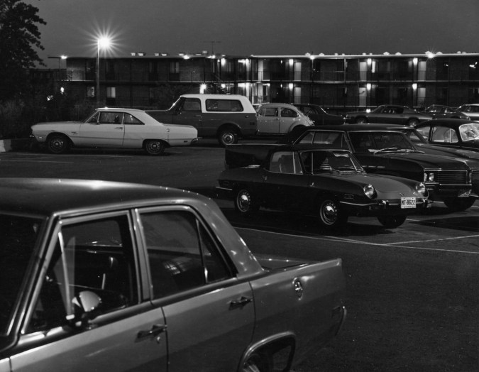 A black and white photograph of a parking lot at night, with 60s cars