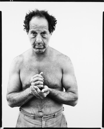 Black-and-white photograph of a shirtless man from the waist up against a white background