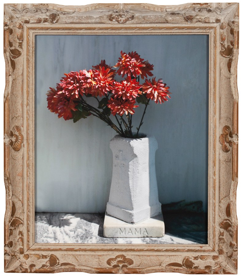 """A photograph of flowers in a white vase engraved with """"MAMA"""" in an ornate frame"""