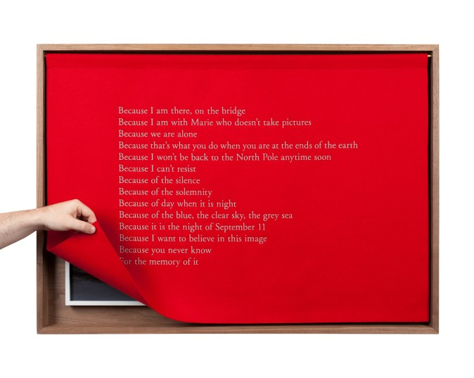 A wooden box with a red felt curtain with white embroidered text, describing the experience of being at the North Pole, the Curtain lifted at the corner by a hand