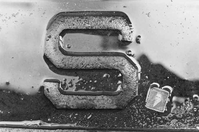 Black and white photograph of a detail of the letter S with water around it and a stamp in the bottom right corner