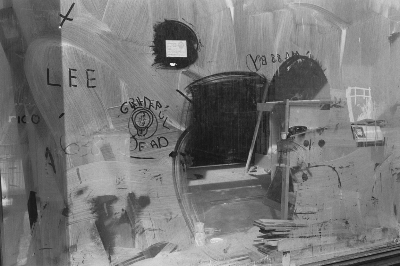 Black and white photograph of a storefront window with graffiti