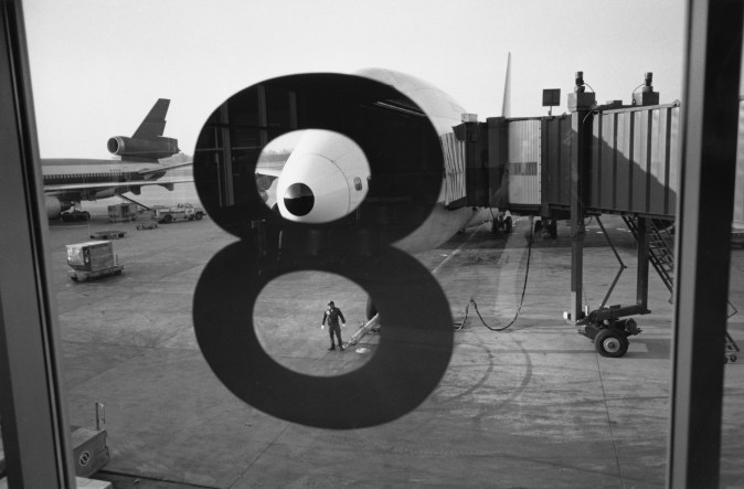Black and white photograph looking out an airport window with the number 8 on it