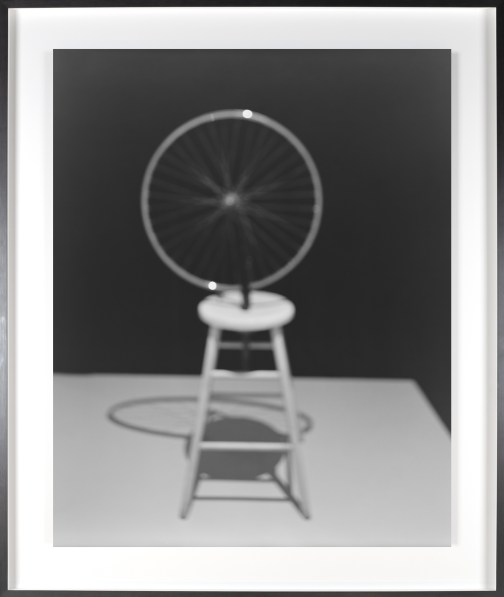 Black-and-white photograph of out of focus sculpture of a bicycle wheel attached to a stool