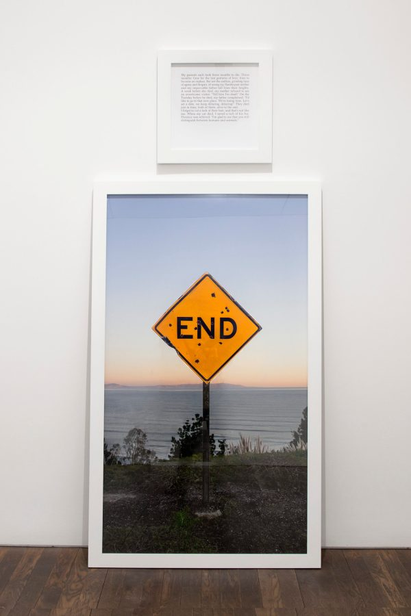 """A small square framed text panel hanging over a large framed photograph of a road sign reading """"END"""""""