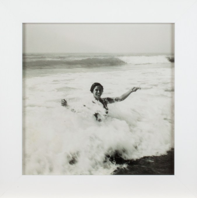 A framed square black and white photograph of a woman in the ocean