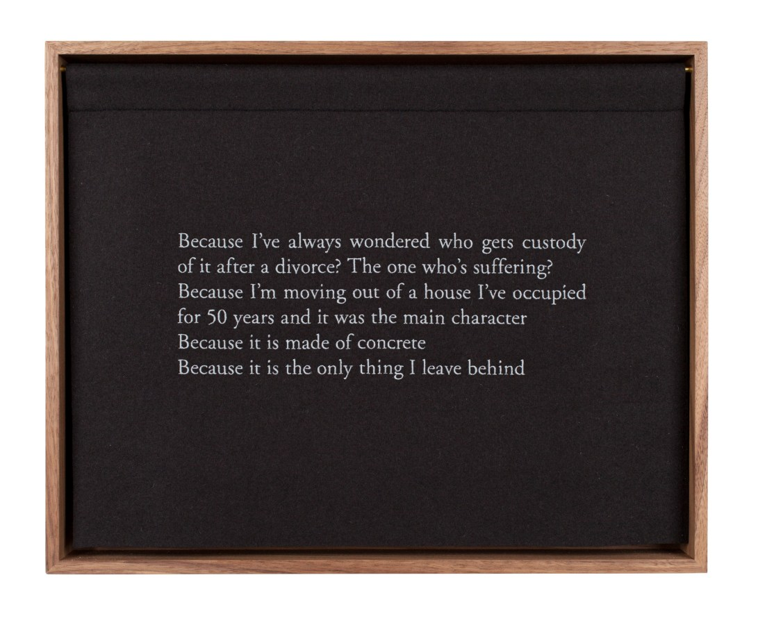 A wooden box, with a black curtain, embroidered with white text, describing a bed