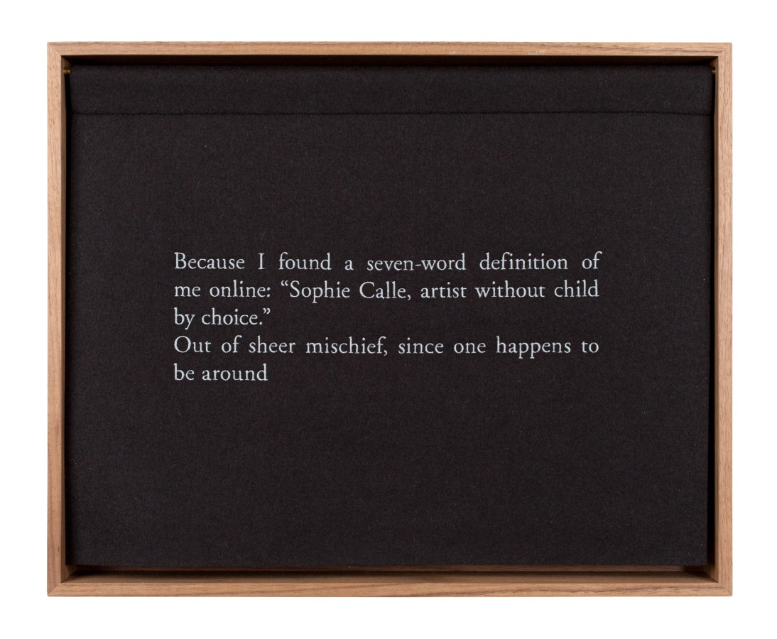 A wooden box with a black curtain, embroidered with white text, describing the artist