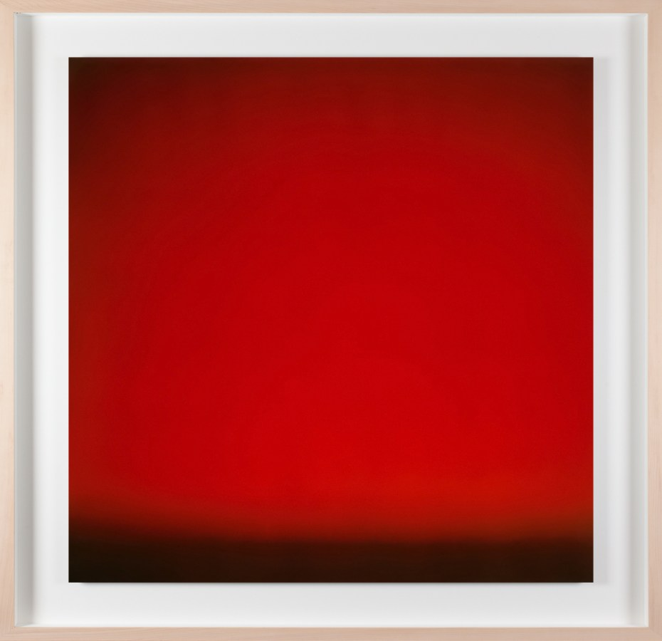 A framed photograph of a red color field, with black line at bottom