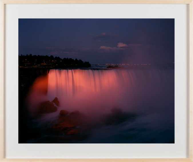 A framed photograph of the Niagara falls at sunset, bathed in pink light