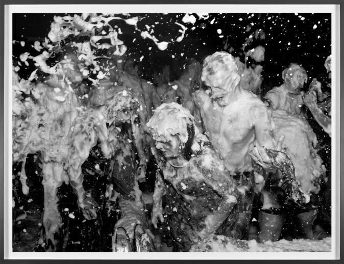 A framed black and white photograph of people dancing, covered in soap foam