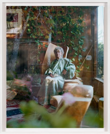 A framed photograph of an elderly woman as seen through a window