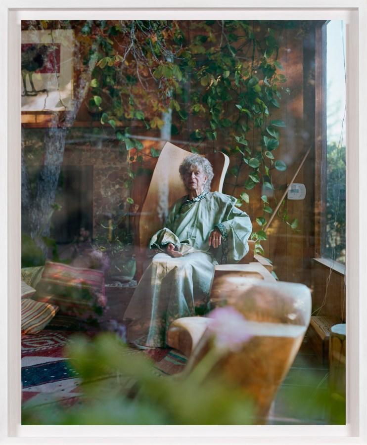 A framed photograph of an elderly woman as seen through a window