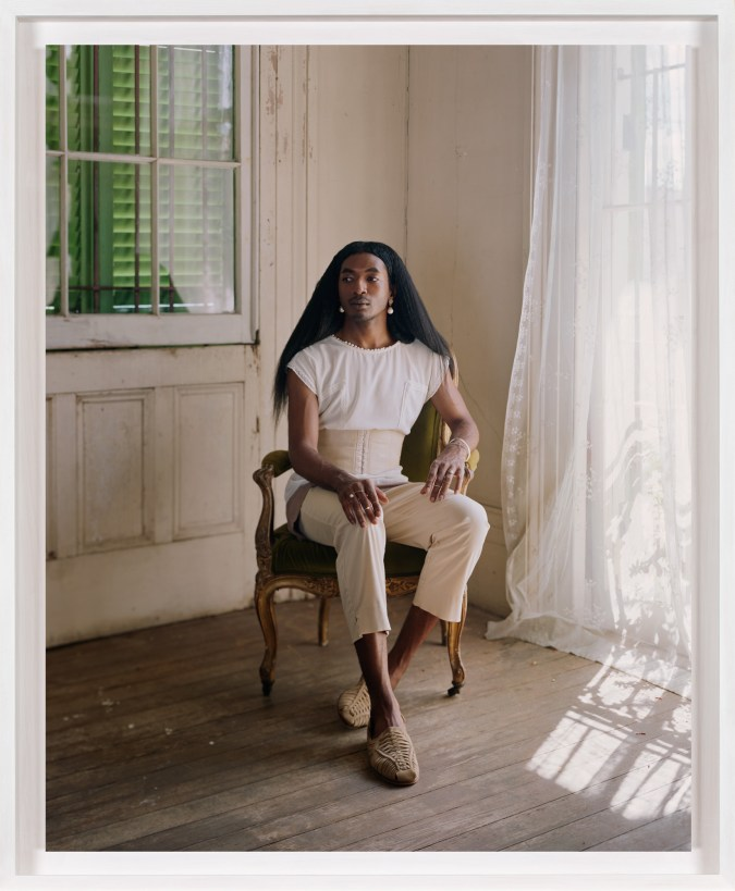 A framed photograph of a person in a chair in the corner of a room with transparent white curtains