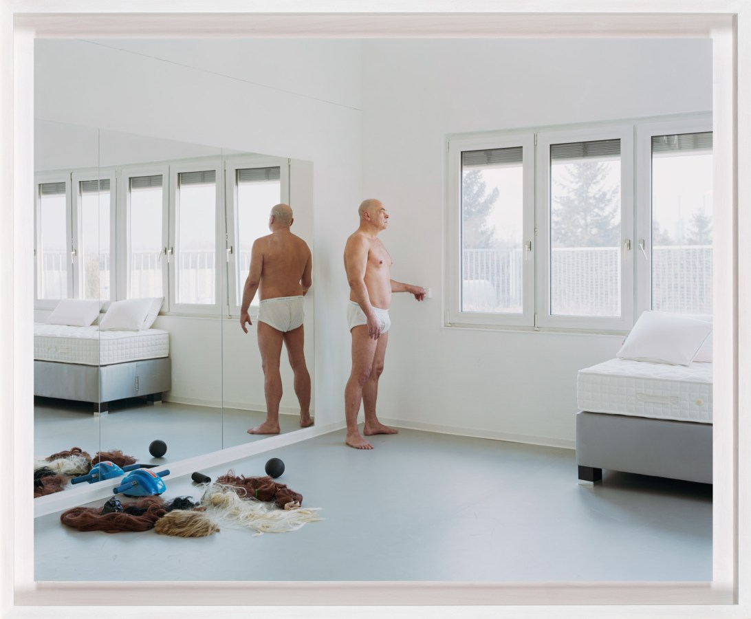 A framed photograph of a man, wearing only his underwear, standing in a plain white bedroom in front of a mirror