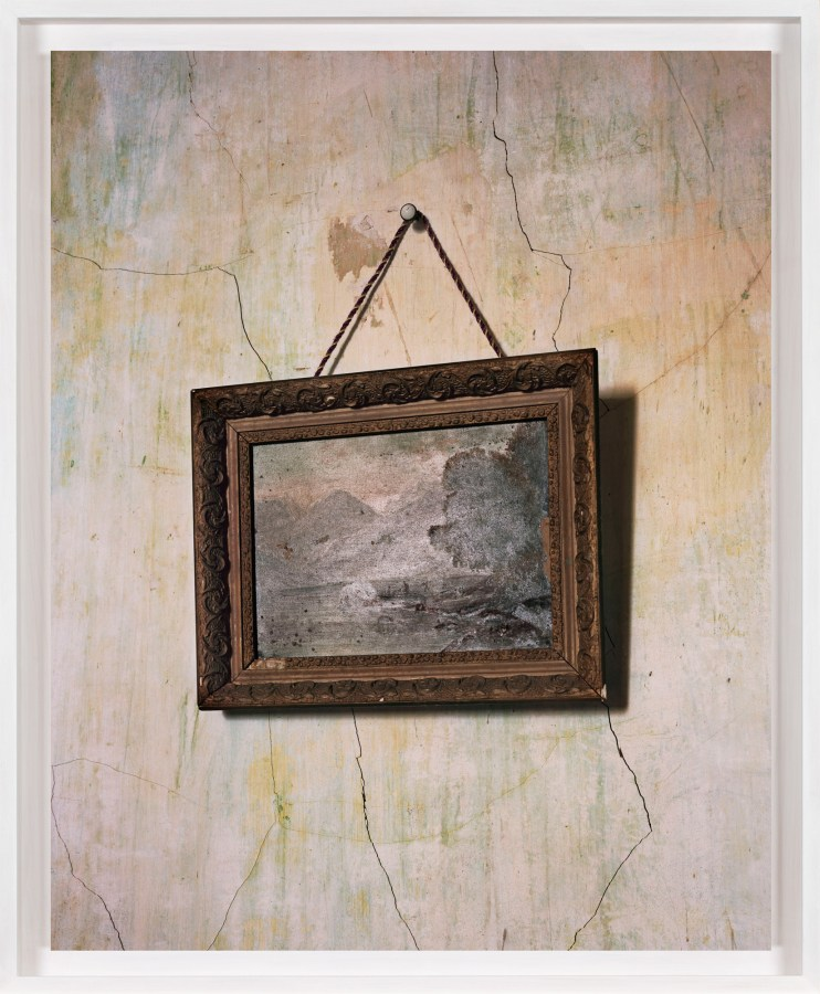 A framed photograph of a painting against a faded, cracked wall