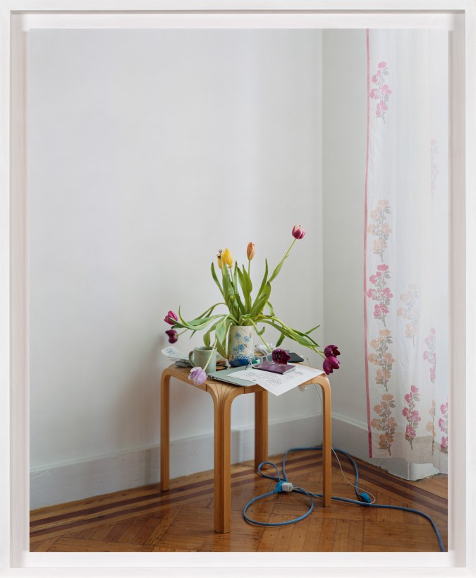 A framed photograph of a small table, with a vase of tulips, a laptop and a coffee cup on top