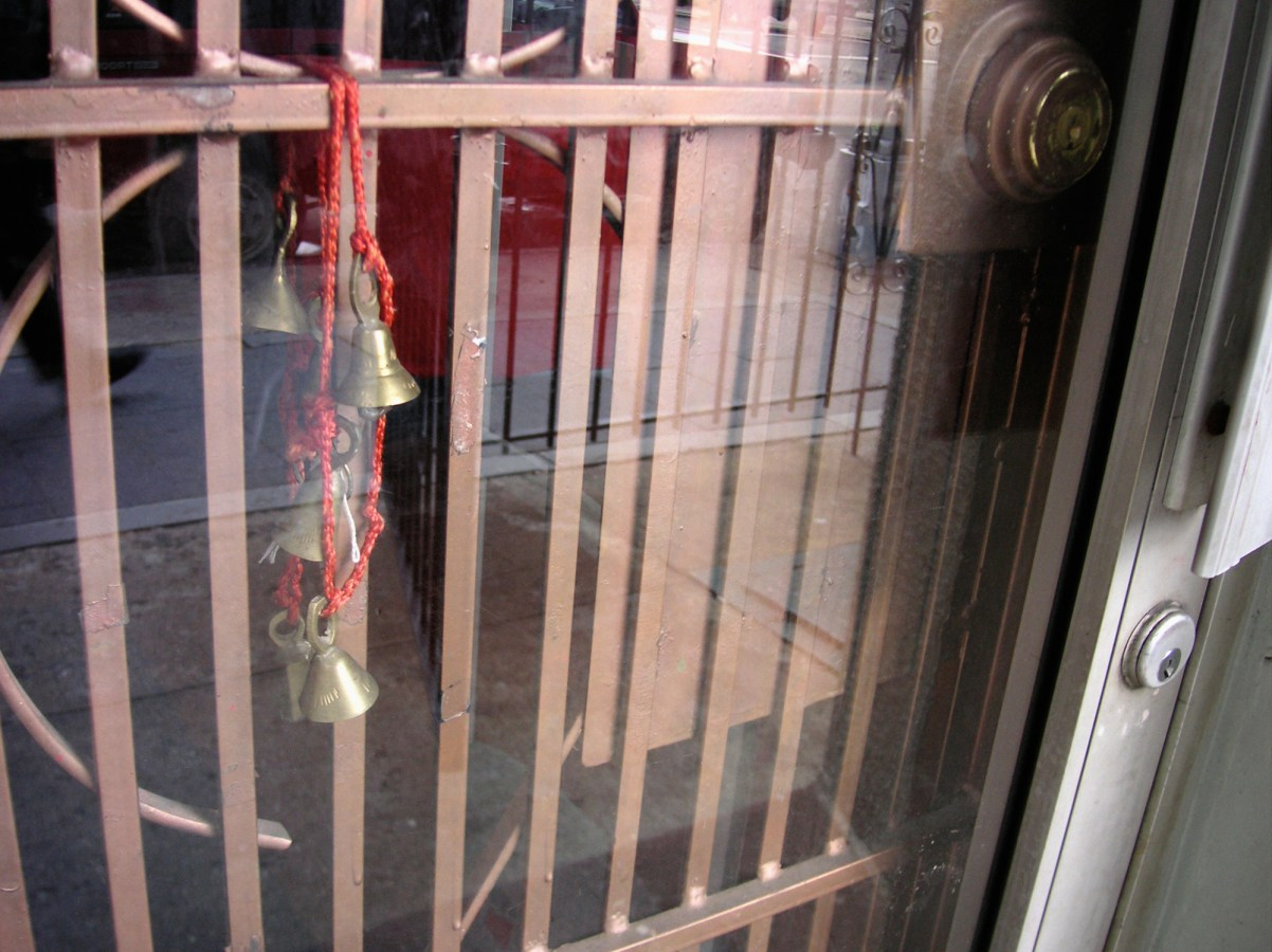 A photograph of bells on a red lanyard, strung on a gate.
