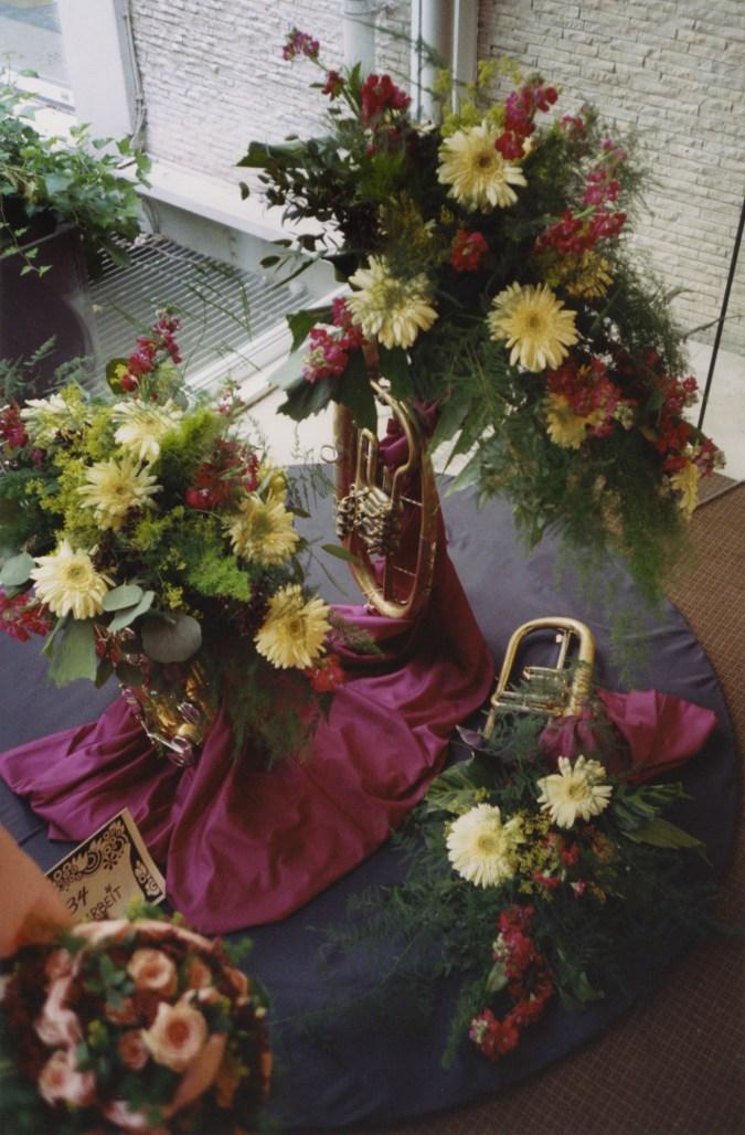 A photograph of flower arrangements, made inside various brass instruments.