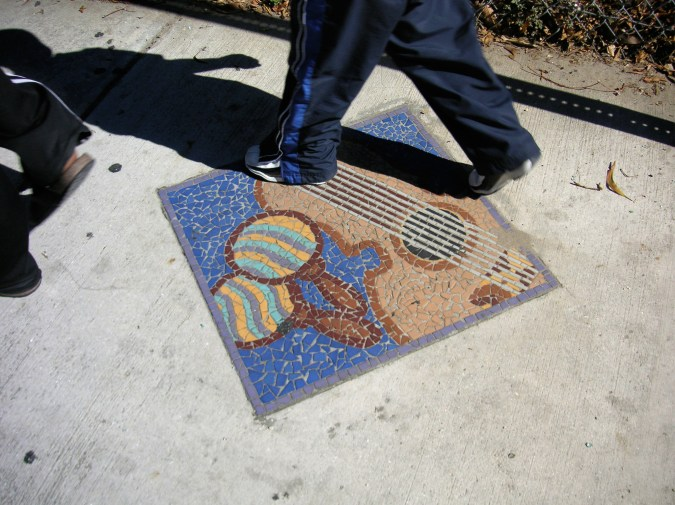 A color photograph of someone walking on a mosaic of a guitar and maracas