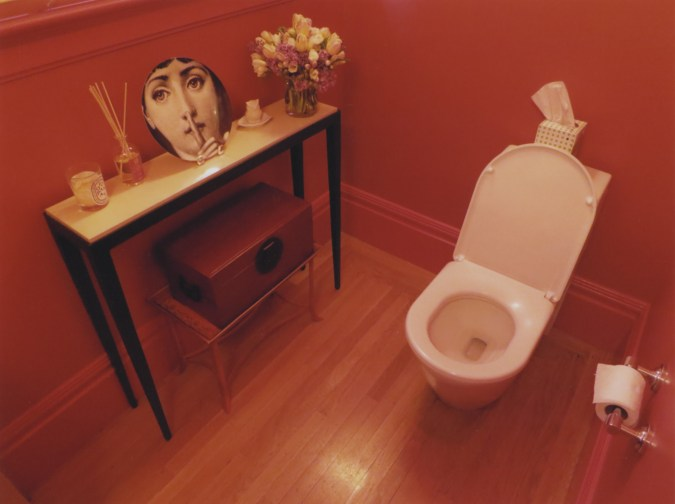 A color photograph of a toilet in a red-painted bathroom