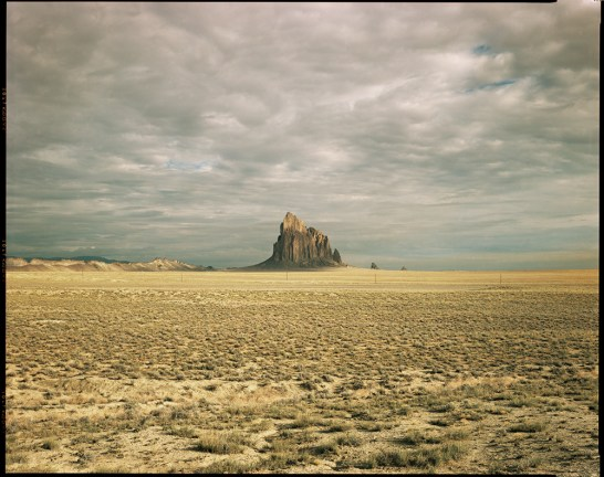 Color photograph of a flat yellow desert landscape under an overcast sky with a tall jagged rock formation rising above the horizon
