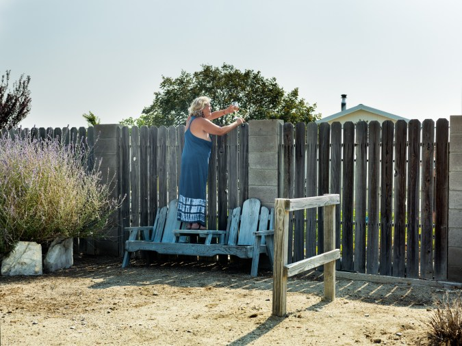 Color photograph of woman in blue dress standing on blue bench, holding a wine glass, looking over a fence.