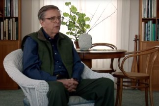Video still of a man seated in an armchair during an interview